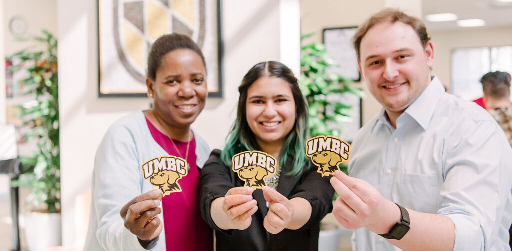 Three students standing side by side holding up the UMBC logo.